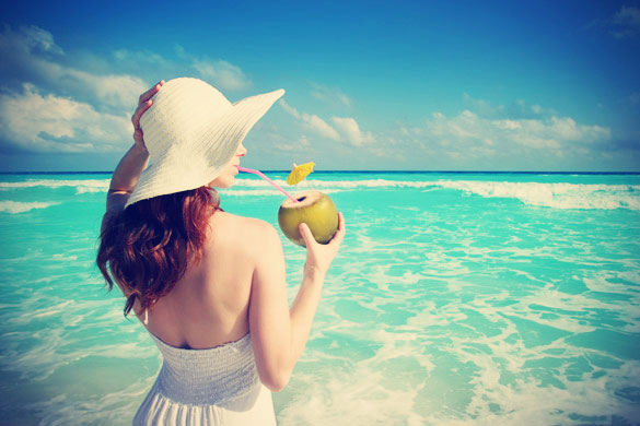 Woman-looking-at-the-ocean-and-drinking-Coconut-Water